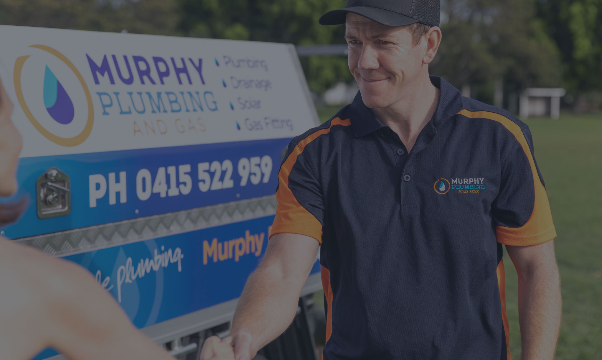 smiling plumber todd murphy shaking clients hand